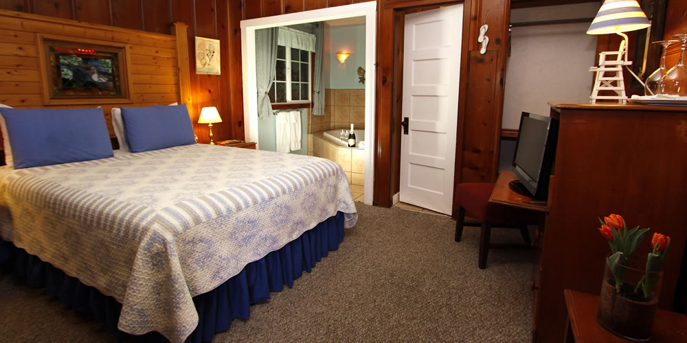 fern grove cottages guest room with bed, seating, flat screen tv and some spa tubs